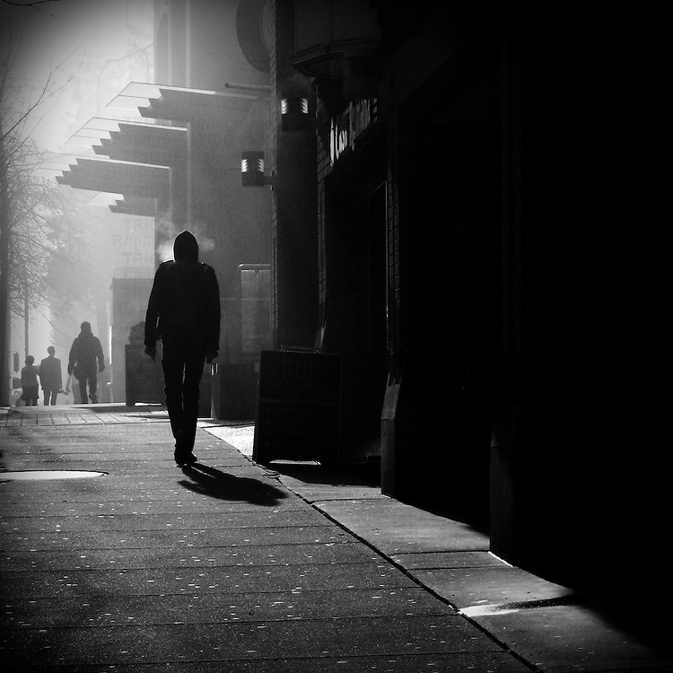 A silhouetted figure with a shadow walking along sidewalk in a foggy city. Three silhouetted figures up ahead.