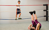 """Christopher """"Mad Man"""" Miller, 9, watches fellow wrestling student Mandy Kantor practice back falls in the ring during wrestling class with Championship Wrestling Entertainment at its gym at 1035 SW Biltmore St. in Port St. Lucie on Wednesday, April 22, 2015. (XAVIER MASCAREÑAS/TREASURE COAST NEWSPAPERS)"""