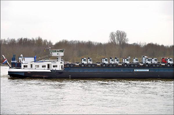 Nederland, Rijn, Waal, 8-4-2015 Binnenvaartschip, autovervoer op de waal, rijn, richting Rotterdam. Vrachtwagens, trekkers staan op het dek van een rollonrolloff, roro, schip. Foto: Flip Franssen/Hollandse Hoogte