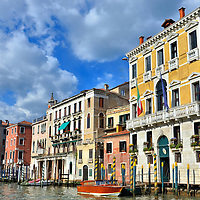 Colorful Mooring Poles on Grand Canal in Venice, Italy<br /> During your first ride down the Grand Canal in Venice, you will be in awe of the colorful buildings clinging to the waterline. They are called a palazzo or palace. Most were built by wealthy aristocrats. In front of them are mooring poles. These pali are used to secure boats. The colors of the stripes represent the family who originally owned the residence.
