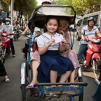 A student and grandmother in a pedicab in Ho Chi Minh City, Vietnam.