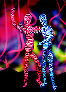 Glowing Mannequins stand in front of a color background.Black light