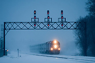 Emerging out of a cloud of snow, an express Metra commuter train blasts through a late evening snowstorm in suburban Elmhurst, IL.