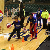 Libby Ezell | BUY AT PHOTOS.DJOURNAL.COM<br /> Evan Cagle, 9, dribbles through cones with Harlem Globetrotter Rocket at Saturday's meet and greet with the team