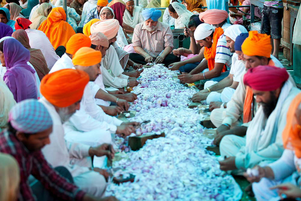 Volunteers cut onions at a Sikh kitchen in Amritsar,Punjab,India.The sikh kitchen at the Golden temple provides ten of thousands of free meals on a daily basis. The main work force at the Sikh kitchen is made of Sikh volunteers.