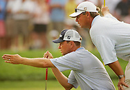 Davis Love III (L) and his caddie John Burke (R) line up a putt on the 18th green at the end of the third round of the 2005 PGA Championship in which Love shot 2 strokes under par at Baltusrol Golf Club in Springfield, New Jersey, Saturday 13 August 2005. Love and Phil Mickelson are now tied for the lead in the competition, each shooting 6 strokes under par.