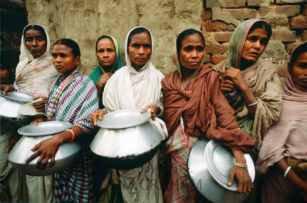 Women carrying pots in early morning food queue at Mother Teresa's Mission in Calcutta, India