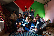 Mahmoud and his family sit inside their home inside the camp with the Palestinian flag on the wall.