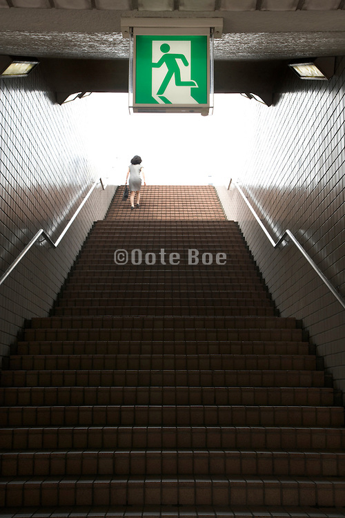 one woman walking up a long stairs