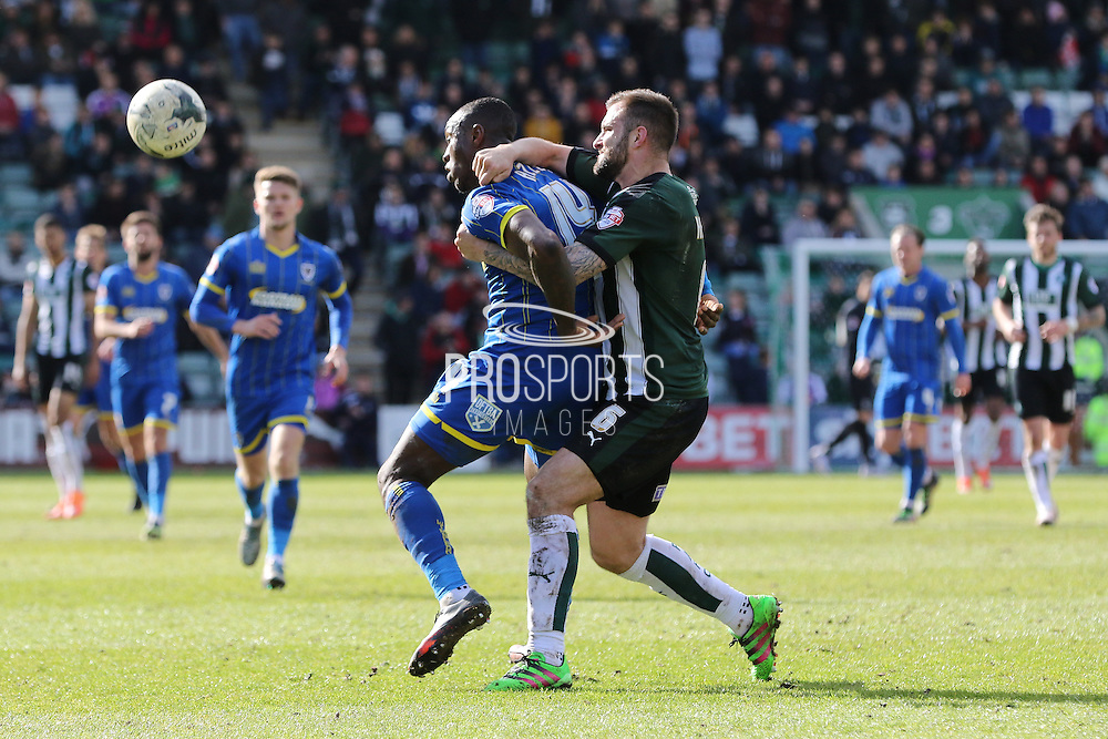 Ade Azeez forward for AFC Wimbledon (14) and Plymouth Argyle defender Peter Hartley (6) tussle during the Sky Bet League 2 match between Plymouth Argyle and AFC Wimbledon at Home Park, Plymouth, England on 9 April 2016. Photo by Stuart Butcher.