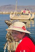 Indigenous woman, reed boat, Isla Los Uros, Puno, Peru