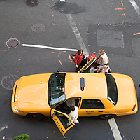 People getting in a yellow cab on 27th street, New York, USA.