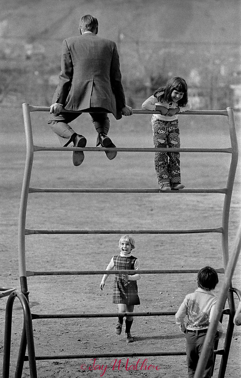 "A student at Peck Elementary School in Arvada, CO reacts with glee as her father sits on top of a climbing structure. It was ""Dad's Day"" at the school, 1974."
