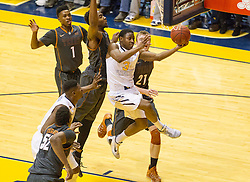 West Virginia Mountaineers guard Juwan Staten (3) drives between two Texas Longhorn defenders during the second half at the WVU Coliseum.