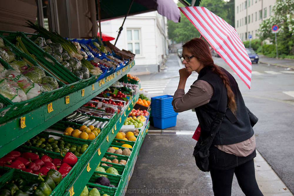 Faith looking at fresh vegetables and fruits at a corner store in Oslo, Norway.