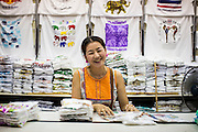 16 FEBRUARY 2013 - BANGKOK, THAILAND:    A tee shirt vendor in Chatuchak Weekend Market in Bangkok. It is reportedly the largest market in Thailand and the world's largest weekend market. Frequently called J.J., it covers more than 35 acres and contains upwards of 5,000 stalls.        PHOTO BY JACK KURTZ