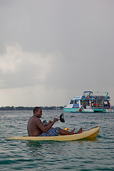 Man in the Bahamas on a Kayak with the Blue Manta in the Background.