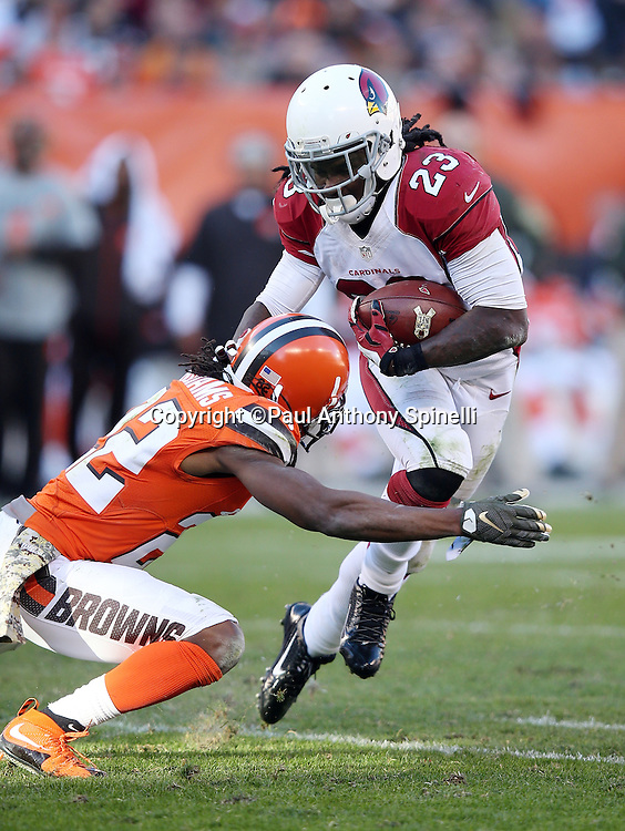 Arizona Cardinals running back Chris Johnson (23) gets tackled by Cleveland Browns cornerback Tramon Williams (22) as he runs the ball in the fourth quarter during the 2015 week 8 regular season NFL football game against the Cleveland Browns on Sunday, Nov. 1, 2015 in Cleveland. The Cardinals won the game 34-20. (©Paul Anthony Spinelli)