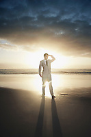 Business man standing on beach against sunset
