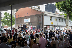© Licensed to London News Pictures. 18/06/2017. London, UK. An outdoor gospel church service takes place under the A40 road flyover and in site of the burnt out Grenfell tower block . The blaze engulfed the 27-storey building killing dozens - with 34 people still in hospital, many of whom are in critical condition. The fire brigade say that they don't expect to find anyone else alive. Photo credit: Peter Macdiarmid/LNP