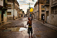 Andris Trujillo, 8, tosses a yellow balloon into the air on August 15, 2015 in the impoverished Cerro Hill neighborhood of Havana, Cuba. At this time, there was an air of hopefulness in the air as talks were held between the United States and Cuban governments for the first time in more than five decades. Cubans hoped that a thawed relation would bring them a better life. (photo by Sarah L. Voisin/The Washington Post)