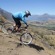 Bradley Dent from Christchurch in action during the New Zealand South Island Downhill Cup Mountain Bike series held on The Remarkables face with a stunning backdrop of the Wakatipu Basin. 150 riders took part in the two day event. Queenstown, Otago, New Zealand. 9th January 2012. Photo Tim Clayton