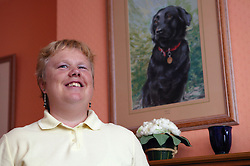 Partially sighted woman with an oil painting of her guide dog,