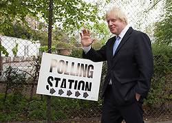 © Licensed to London News Pictures. 03/05/2012. LONDON, UK. London Mayor Boris Johnson walks past a sign for a polling station  in Islington, North London, after casting his vote in the 2012 mayoral and council elections. Photo credit: Matt Cetti-Roberts/LNP