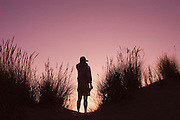 Man checking the view from the top of the sand dune at sunset; Carter Lake Campground, Oregon Dunes National Recreation Area, Oregon coast