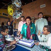 FAIRFAX, VA -DEC21: Emerita Ayala, 23, cuts her graduation cake during a party with friends and family, including her son Dominic, 8, (right), and brother Christopher, 6, (left), at Guapos restaurant, celebrating her graduation from George Mason University, December 21, 2016, in Fairfax, Virginia. Emerita started as a teenage mom at 18, with her 3-year-old son at community college. She got help through a nonprofit called Generation Hope that provides scholarships and mentoring to teenage moms. (Photo by Evelyn Hockstein/For The Washington Post)