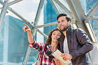Portrait of young attractive couple looking on the map in the middle of the city