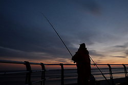 © Licensed to London News Pictures. <br /> 08/10/2014. <br /> <br /> Saltburn, United Kingdom<br /> <br /> A fisherman stands on the pier as the day dawns at Saltburn beach in Cleveland.<br /> <br /> Photo credit : Ian Forsyth/LNP