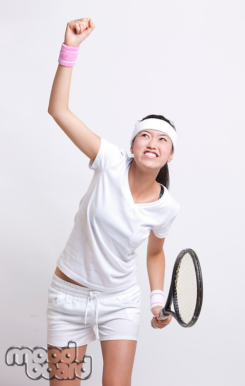 Young Asian female tennis player celebrating her success against white background