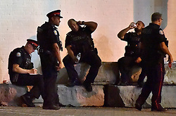 Police officers rest at the scene of a mass casualty incident in Toronto, ON, Canada on Sunday, July 22, 2018. A young woman has been killed and 13 others injured in a shooting incident in Toronto, Canadian police say. The Sunday night shooting happened in the Danforth and Logan avenues area. The gunman died in an exchange of fire. Among those injured is a young girl, described as in a critical condition. Police are appealing for witnesses. Photo by Frank Gunn/ABACAPRESS.COM