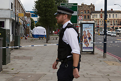 © Licensed to London News Pictures. 11/08/2014. London, UK. The murder investigation scene in Eltham Road, Lee in South East London where a man is reported to have been stabbed last night. Photo credit : Vickie Flores/LNP
