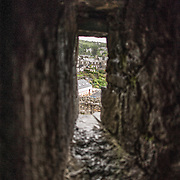 View of the town from one of the archers' windows at Harlech Castle in Harlech, Gwynedd, on the northwest coast of Wales next to the Irish Sea. The castle was built by Edward I in the closing decades of the 13th century as one of several castles designed to consolidate his conquest of Wales.