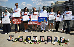 © Licensed to London News Pictures. 03/06/2018. London, UK. Campaigners from Turn To Love hold up personal signs, while stood in front of pictures of the eight victims, ahead of a minutes silence for the victims of the 2017 London Bridge Terror attack, held on London Bridge. Eight people were killed and 48 were injured when a van was deliberately driven into pedestrians on London Bridge. Three occupants then ran to the nearby Borough Market area carrying knives and fake explosives. Photo credit: Ben Cawthra/LNP