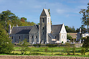 Ancient typical Norman style church with graves in graveyard in village of Vaux-sur-Aure in Normandy