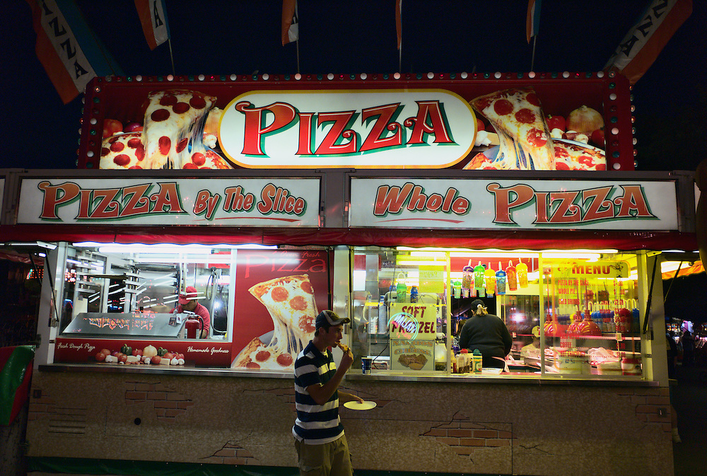 Youth eating slice of pizza in front of pizza stand, Columbia County fair, Chatham, New York