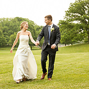 Bride and Groom walk hand in hand through a meadow