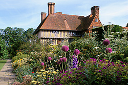 The Long Border and house at Great Dixter in early summer with Allium giganteum and Geranium 'Ann Folkard' in the foreground