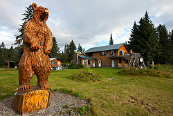 Exterior view of Silver Salmon Creek Lodge with wooden grizzly bear statue, Lake Clark National Park, Alaska, United States of America