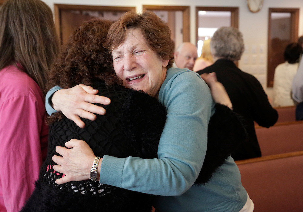 Evie Schwerin hugs a fellow church member during service at the Glad Tidings Assembly of God church in Darrington, Washington March 30, 2014. Local churches offered prayers on Sunday for the victims of last week's devastating mudslide in Washington state and words of solace for grieving families and friends, many of whom are still waiting for news of missing loved ones. The presumed body count stood at 28 from the March 22 catastrophe northeast of Seattle, with the official tally of those killed at 18, based on bodies extricated and identified by medical examiners.  REUTERS/Jason Redmond (UNITED STATES)