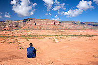 A hiker gazes out from the slickrock to the Straight Cliffs in Grand Staircase-Escalante National Monument, Utah
