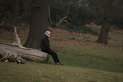 © Licensed to London News Pictures. 20/03/2015. Richmond, UK. A woman sits on a fallen tree to watch.  People watch the cloudy sky darken during the near total eclipse at Richmond Park, Surrey today 20th March 2015. Photo credit : Stephen Simpson/LNP