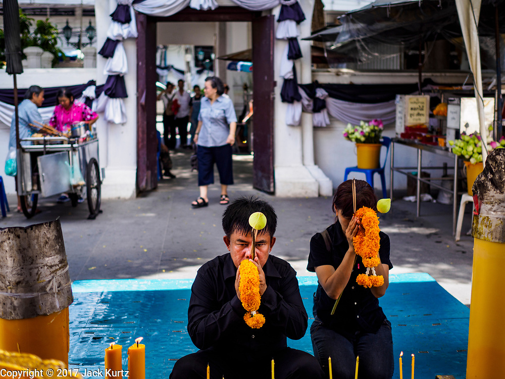 "11 APRIL 2017 - BANGKOK, THAILAND: A man prays at Wat Chana Songkhram in Bangkok during a Songkran merit making service. Songkran is the traditional Thai Lunar New Year. It is celebrated, under different names, in Thailand, Myanmar, Laos, Cambodia and some parts of Vietnam and China. In most places the holiday is marked by water throwing and water fights and it is sometimes called the ""water festival."" This year's Songkran celebration in Thailand will be more subdued than usual because Thais are still mourning the October 2016 death of their revered Late King, Bhumibol Adulyadej. Songkran is officially a three day holiday, April 13-15, but is frequently celebrated for a full week. Thais start traveling back to their home provinces over the weekend; busses and trains going out of town have been packed.     PHOTO BY JACK KURTZ"