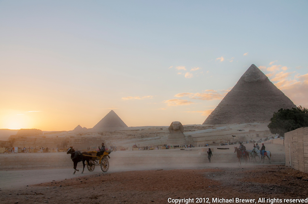 The Giza plateau with pyramids and sphinx, horses and carts at sunset in Egypt.