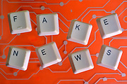 Keyboard keys form the word FAKE NEWS on orange electric circuit in the background.