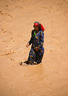 Yemen, Tihama, old woman crossing a Wadi, a river flooded by heavy rains.