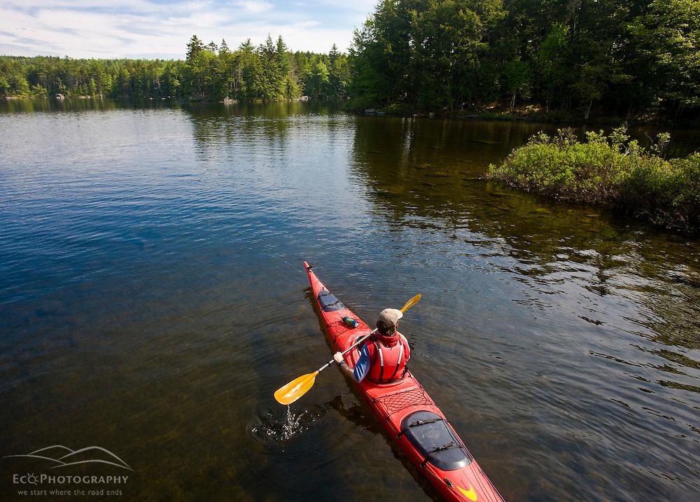A man kayaks on Branch Lake in Ellsworth, Maine.